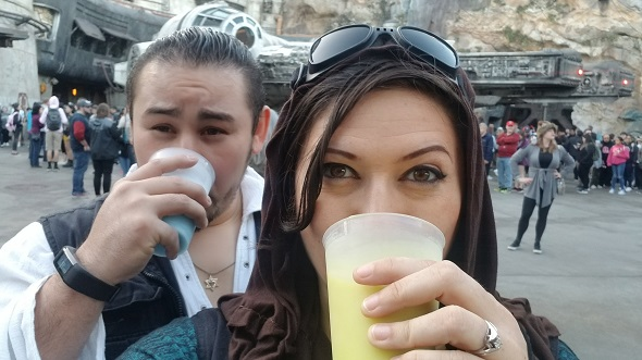 Male and female guests dressed as Batuu locals drinking blue and green milk in front of Millennium Falcon