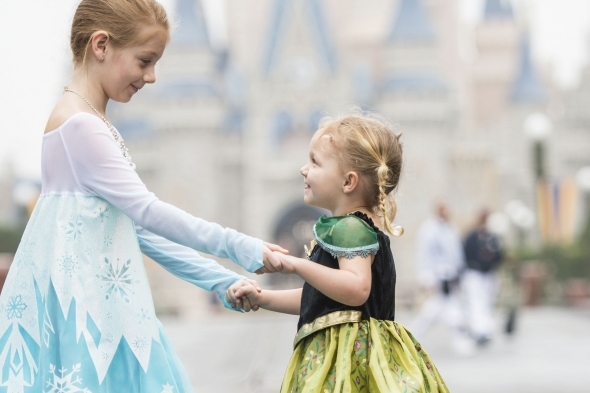 Little girl dressed as Elsa with sister dressed as Anna