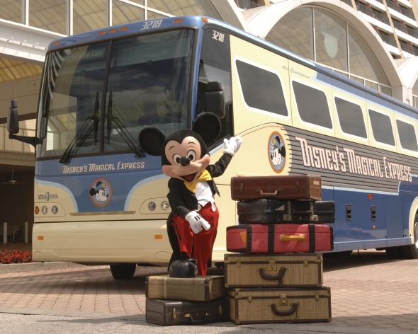 Mickey standing with suitcases next to Magical Express Bus