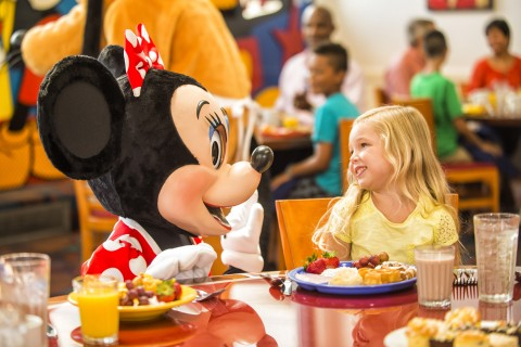 Minnie greeting a little girl at Chef Mickey's