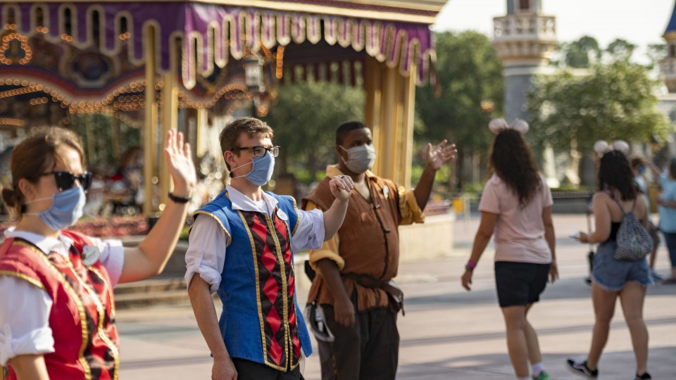 Cast members in masks waving to guests