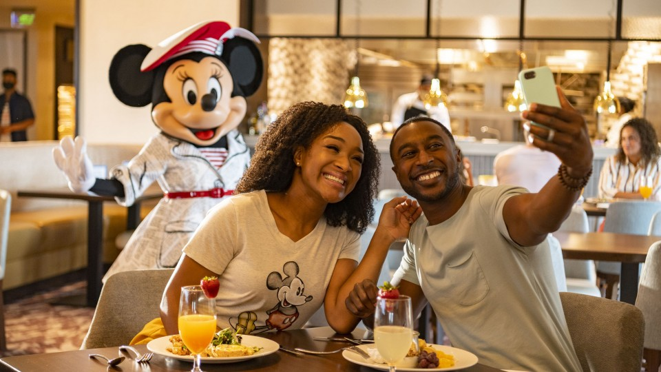 Couple takes a selfie at restaurant with Mickey Mouse waving distanced in the background