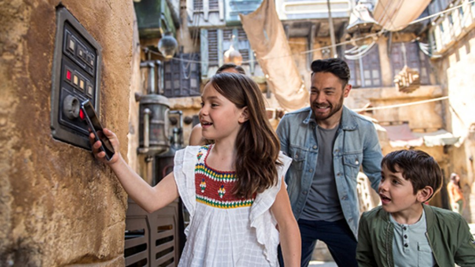 Dad and kids playing Star Wars Datapad in Galaxy's Edge