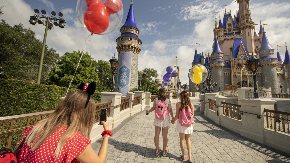 Girls walking away from camera by castle with Minnie Ears and Balloons while friend takes picture