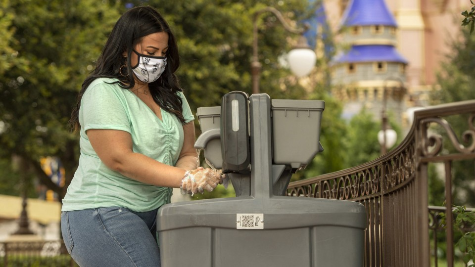 Woman in mask washes hands at outdoor hand washing station