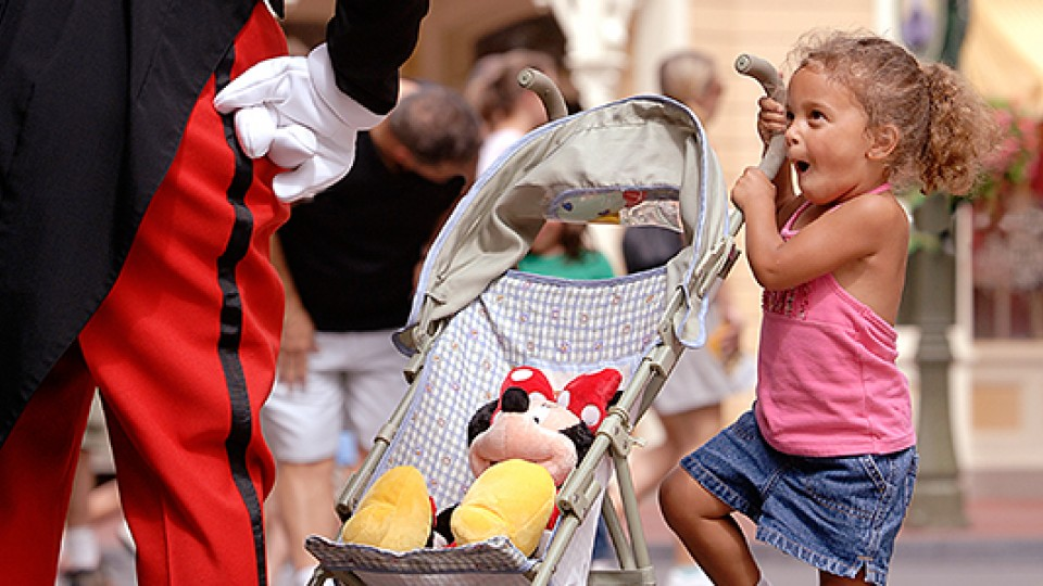 Little girl with stroller standing in front of Mickey
