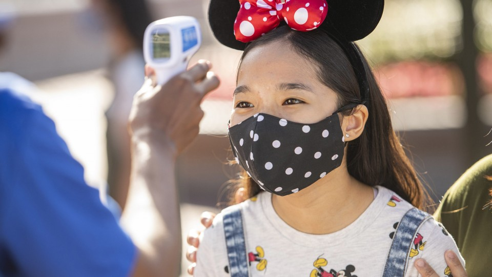 Young girl in Minnie Ears and colorful mask getting temperature check